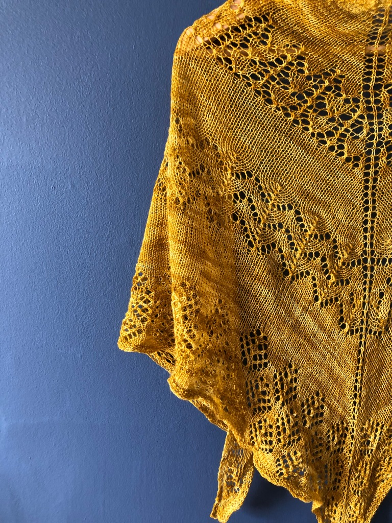 Mustard yellow Beatrice lace shawl against dark blue background