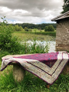 Handknitted red, green, and purple, lace shawl draped in front of a lake.