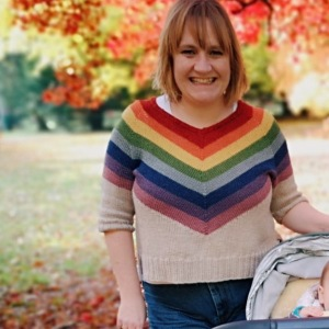 Woman in the woods wearing a v-neck rainbow striped jumper