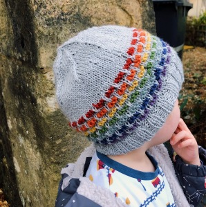 A child wears a grey knitted hat with rainbow-colours stripes.