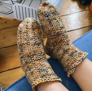 A child's feet in handknitted textured socks.
